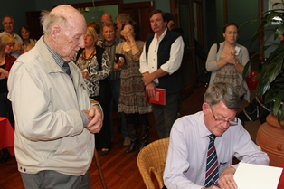 Gerry signs a copy of the book for Len Brown, one of the original case investigators
